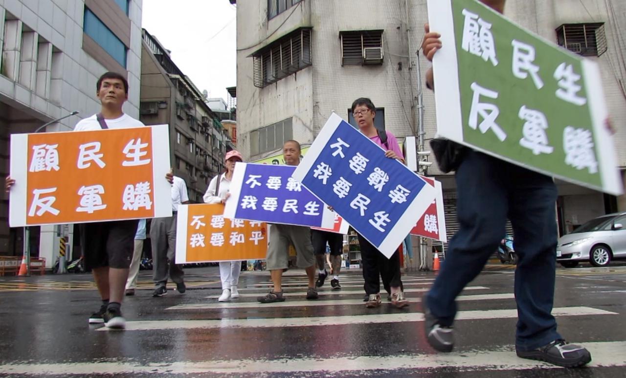 近日有公民團體自發在民進黨部周邊高舉「反軍購、要民生」標語。(攝影:張心華)